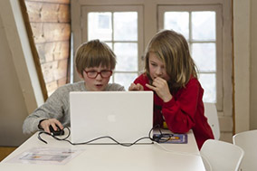 Two children in a house behind the screen of a laptop