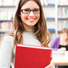 Female student with glasses holding a book in the library