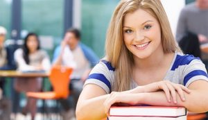 Smiling female student with her arms on top of a book