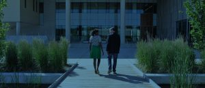Woman and Man walking on a boardwalk towards a campus building