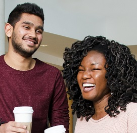 Man holding coffee smiles at laughing woman