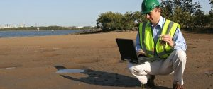 A man in a safety vest crouching on a beach with a laptop on his knee