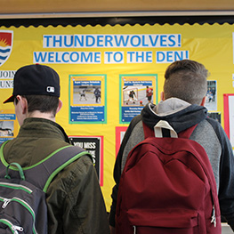 Two male students wearing backpacks in front of a board that says: Thunderwolves! Welcome to the den!