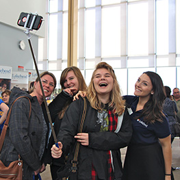 A group of girls using a selfie stick to take a picture of themselves