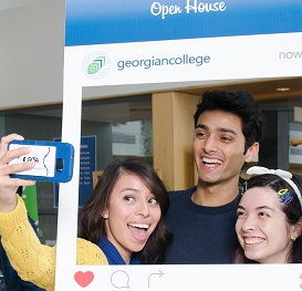 Open house visitors taking a selfie in a cardboard cutout shaped like a social media post