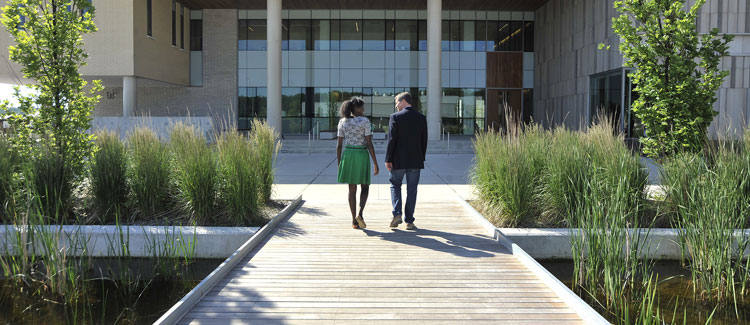 Man and woman walking across boardwalk towards Orillia campus building