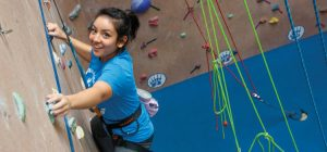 Young female student climbing a climbing wall