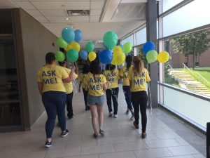Students in yellow Ask me t-shirts holding balloons at the Barrie Campus