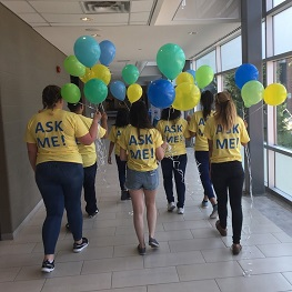 STudents walking through the hall at Georgian wearing Ask Me t-shirts