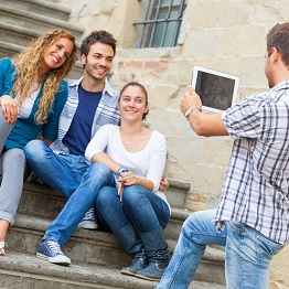 Three students posing a staircase for a photo being taken by another student