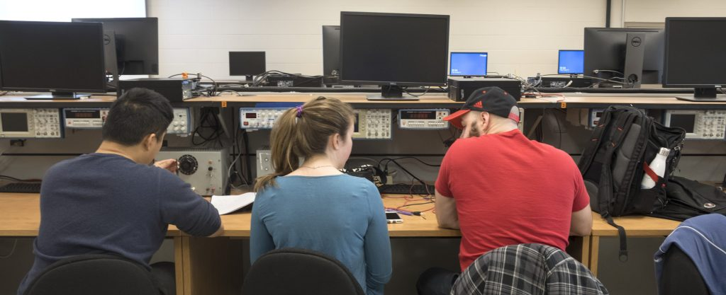 Three students working in an electrical lab (including Jacky).