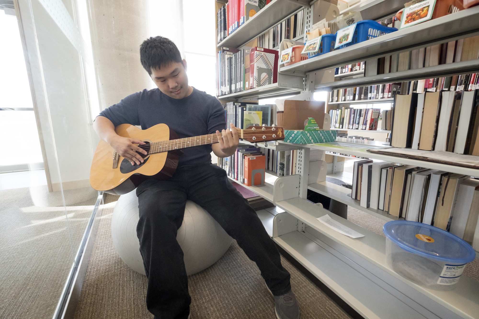Jacky Wu playing the guitar at the library at LU's Orillia Campus