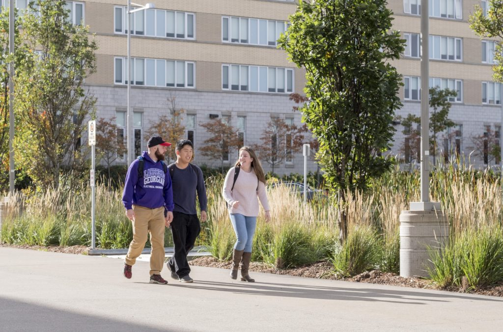 Three students walking on LU campus grounds
