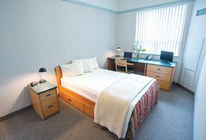 Interior shot of student residence in Barrie, with bed, night table, and desk