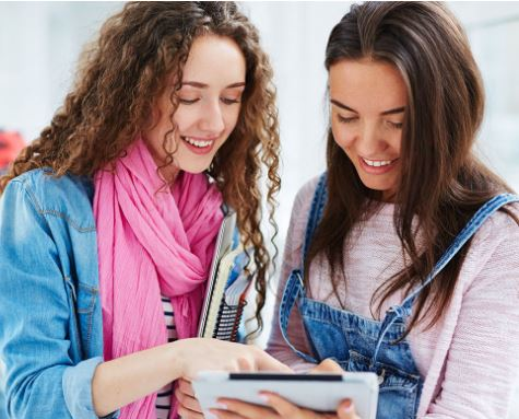 Two students leaning over a tablet