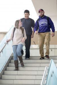 Three students descending stairs