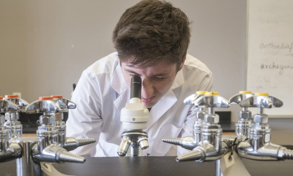 A student looks through the lens of a microscope during a biology class at Lakehead-Georgian