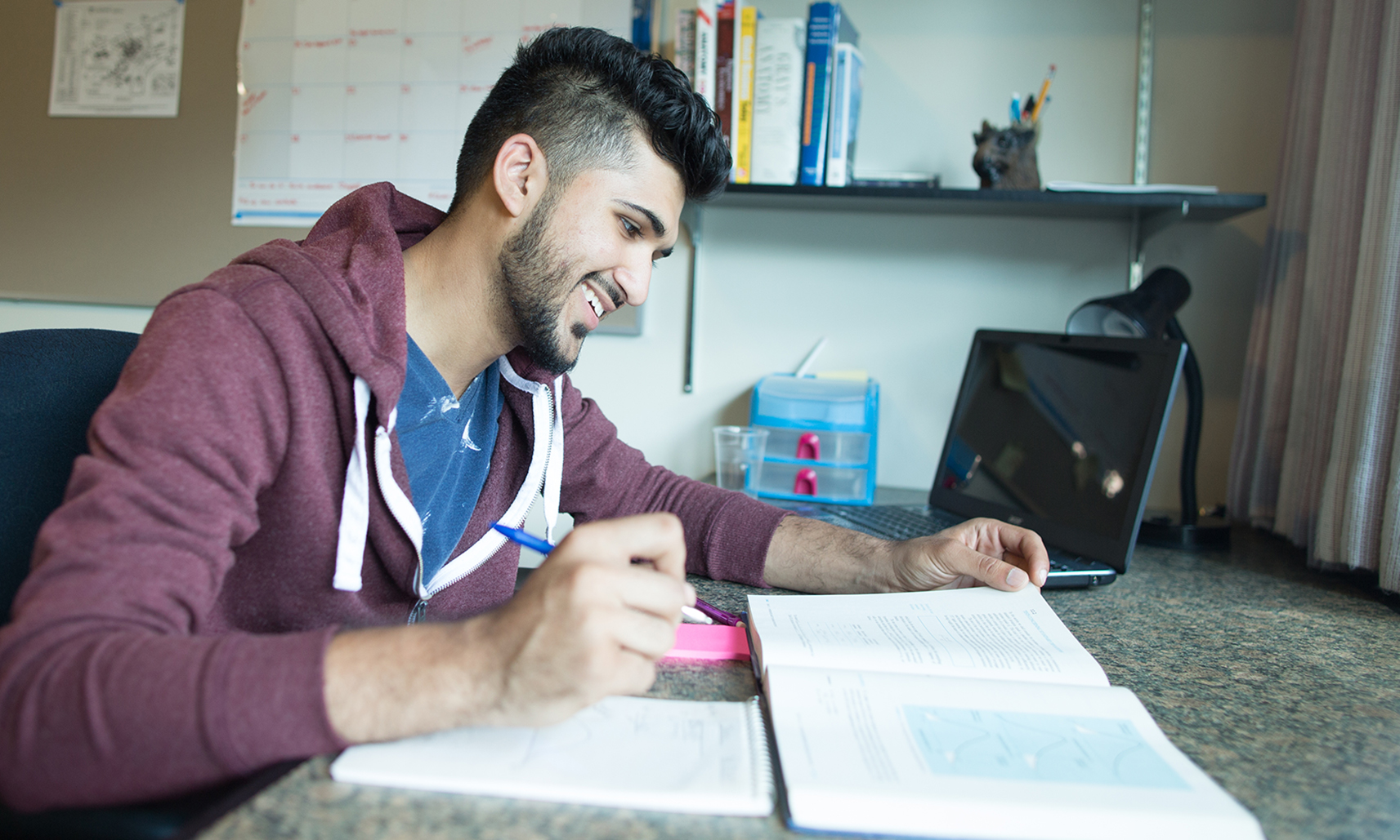 A smiling student is pictured in his residence room sitting at a desk working from a textbook. A black laptop computer and light are pictured in the background.