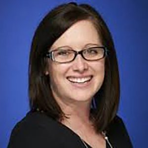 A smiling dark-haired woman with glasses is pictured against a blue background.