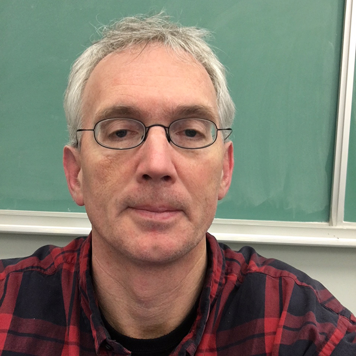 Pictured is Sean Madorin, a silver-haired man with wire-rimmed glasses wearing a flannel shirt, standing in front of a green chalkboard