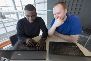 Two male students working on laptops