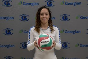 Female volleyball player posing with ball