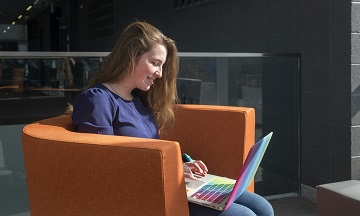 Avery sits in the Advanced Technology Centre in an orange chair, working on her laptop. The sun is shining through the windows.