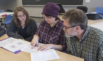 Two students in the Applied Life Sciences program sit at a classroom table, talking with their instructor about their course work