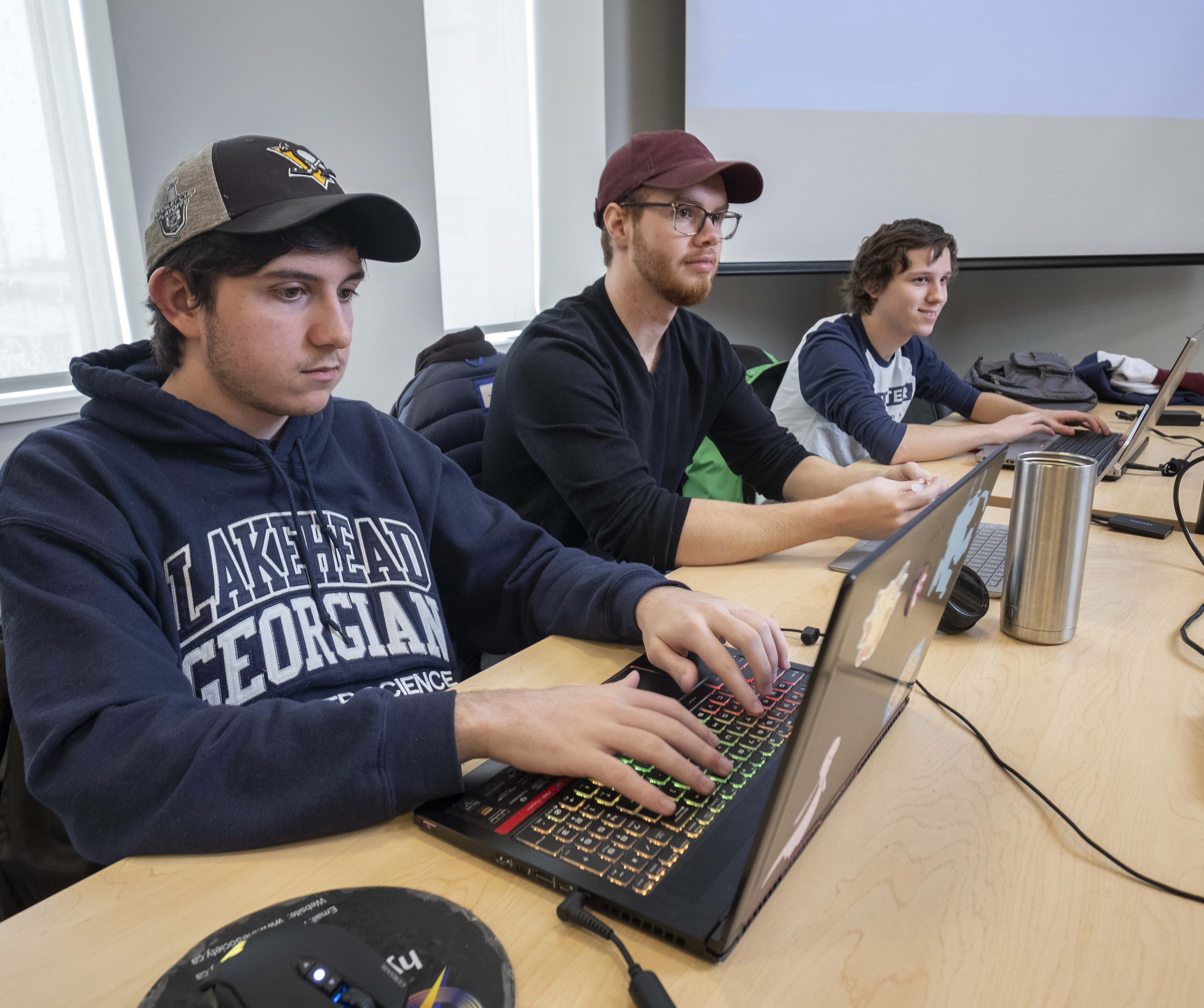 Three male students participate in computer science class
