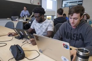Two male students work on their laptops in a computer science class
