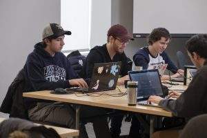 Three male students work on their laptops in computer science class