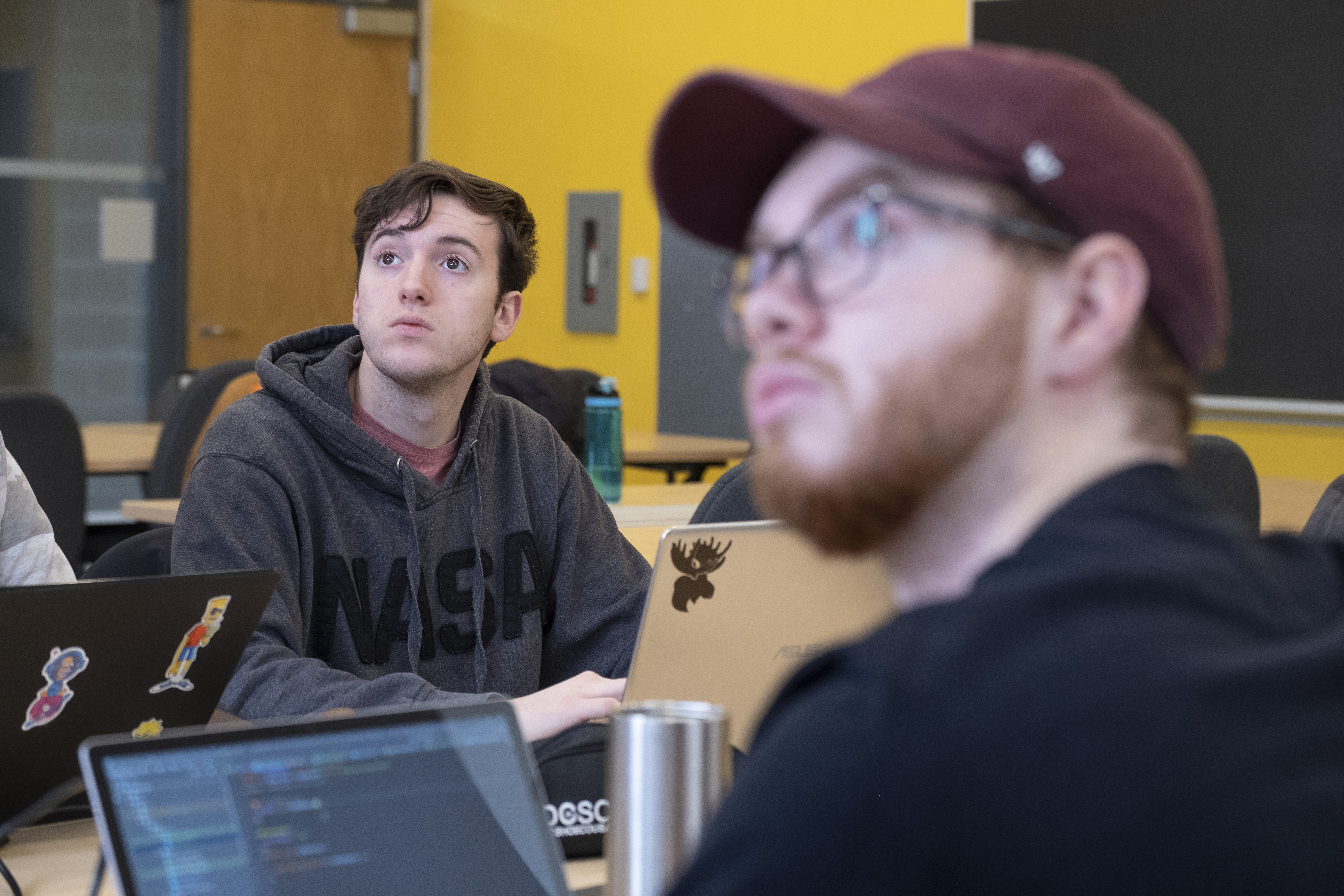 Two male students looking up at instructor in computer science class