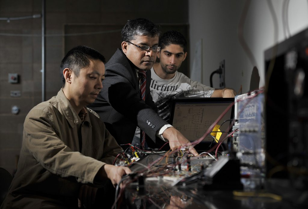 Professor helping students in engineering lab