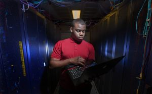 Tolu in data centre on campus with computer