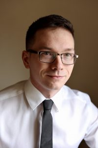 A young man with glasses wears a white dress shirt and tie
