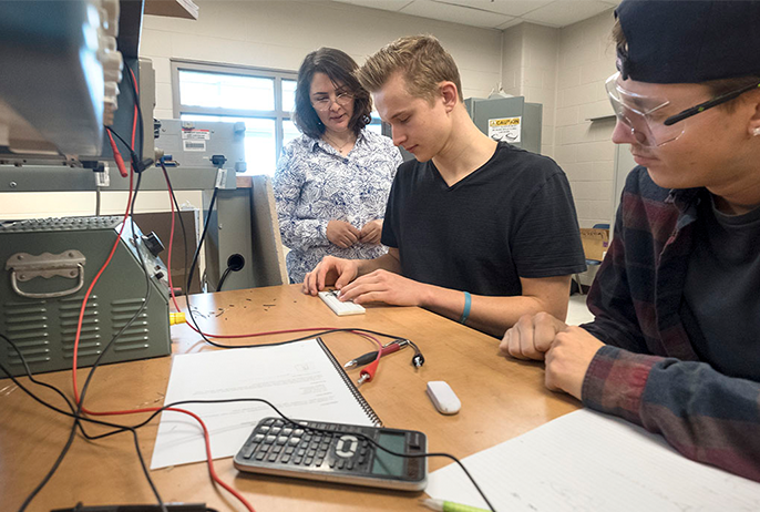 Two students work alongside a faculty instructor in the electrical engineering lab at Georgian College